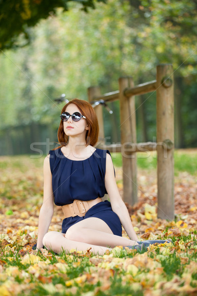 beautiful young woman sitting near wooden fence with bicycle in  Stock photo © Massonforstock
