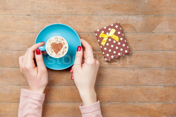 photo of female hands holding cup of coffee near gift on the won Stock photo © Massonforstock