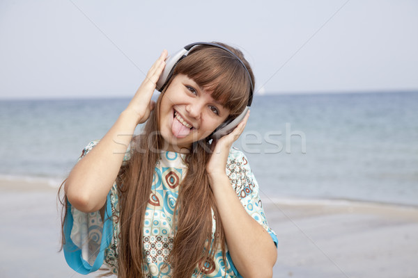Young brunet girl with headphone on the beach. Stock photo © Massonforstock