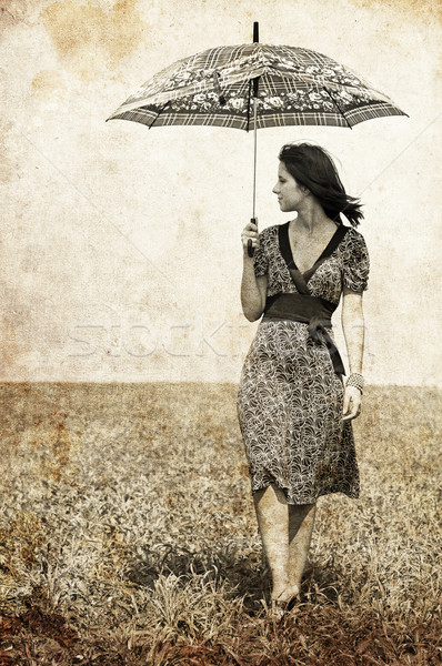 Stock photo: Girl with umbrella on field. Photo in old image style.