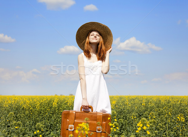 Stock photo: Redhead enchantress with suitcase at spring rapeseed field.