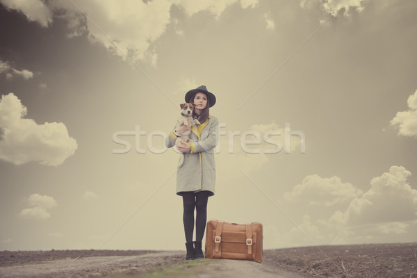 Stock photo: beautiful young woman holding her dog near suitcase on the wonde