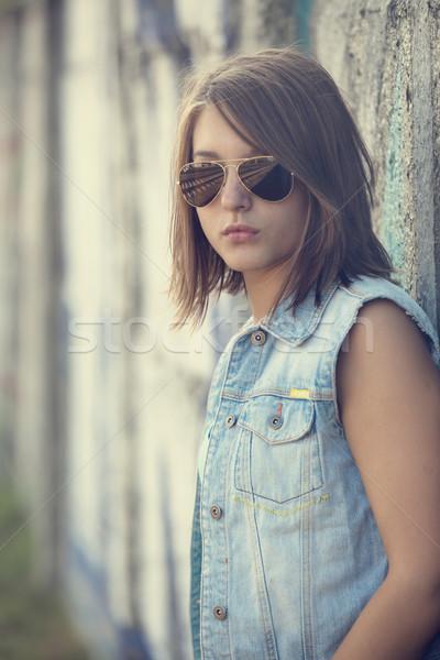 Teen girl in sunglasses near graffiti wall. Stock photo © Massonforstock