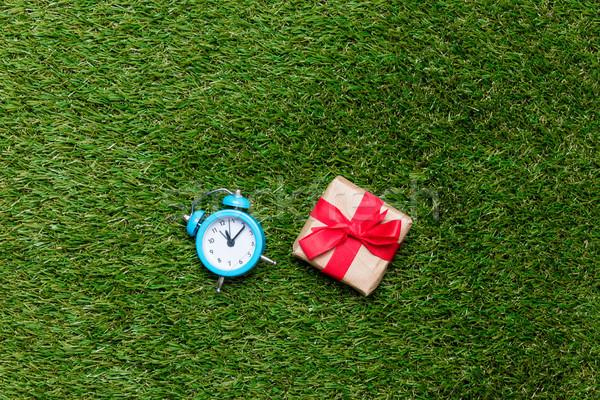 Little retro alarm clock and gift box on green grass background Stock photo © Massonforstock