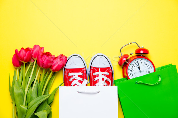 bunch of red tulips, red gumshoes, cool shopping bags and alarm  Stock photo © Massonforstock
