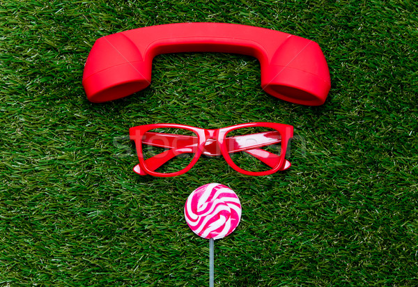 Stock photo: styled red glasses with lollipop and handset on green grass back