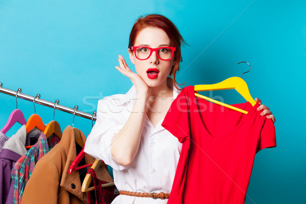 photo of beautiful young woman with shirt on hanger near clothes Stock photo © Massonforstock