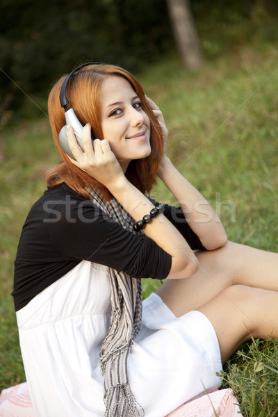 Young fashion girl with headphone sitting at green grass Stock photo © Massonforstock