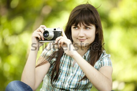 Stock photo: Teen girl with camera at the green park.