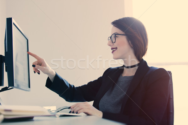 beautiful young woman sitting at the desk and  touching screen i Stock photo © Massonforstock