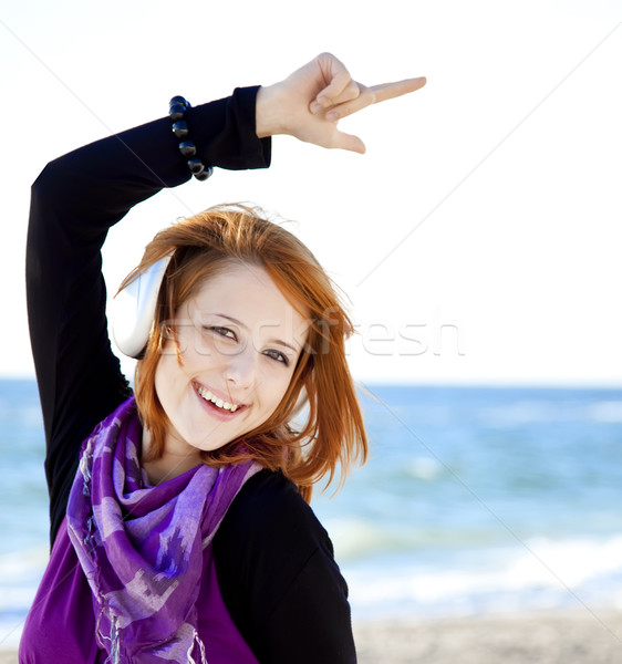 Portrait of red-haired girl in cap with headphone on the beach.  Stock photo © Massonforstock