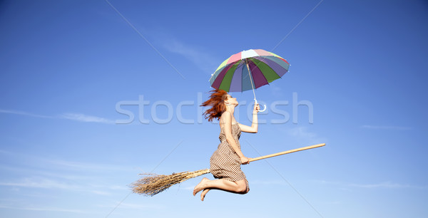 Young red-haired witch on broom flying in the sky with umbrella  Stock photo © Massonforstock