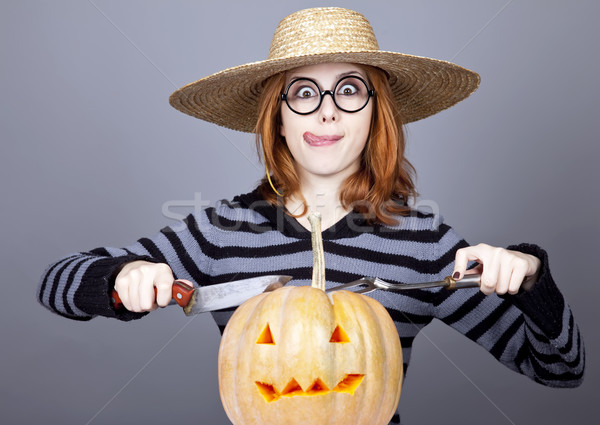 Funny girl in cap and fork with knife try to eat a pumpkin.  Stock photo © Massonforstock