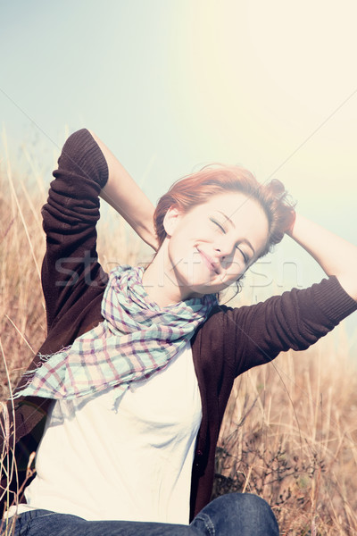 Portrait of happy red-haired girl on autumn grass. Stock fotó © Massonforstock