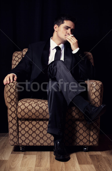 Man with cigarette sitting in vintage armchair Stock photo © Massonforstock