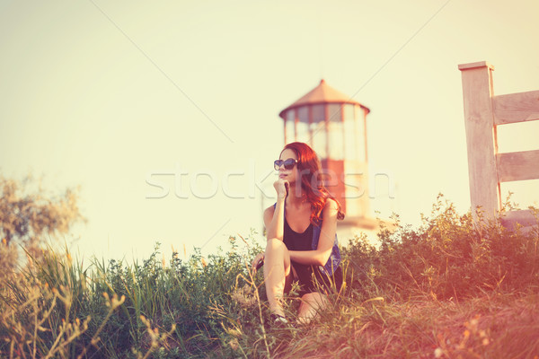 Stock photo: girl sitting on the grass near Lighthouse