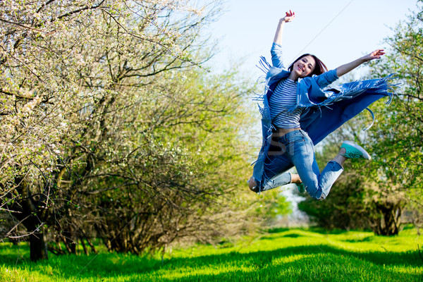 beautiful young woman jumping in front of blooming green garden Stock photo © Massonforstock