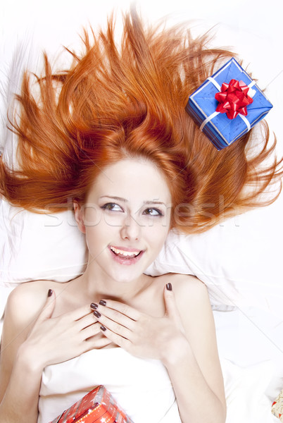 Happy red-haired girl in bed with Christmas gifts. Stock photo © Massonforstock