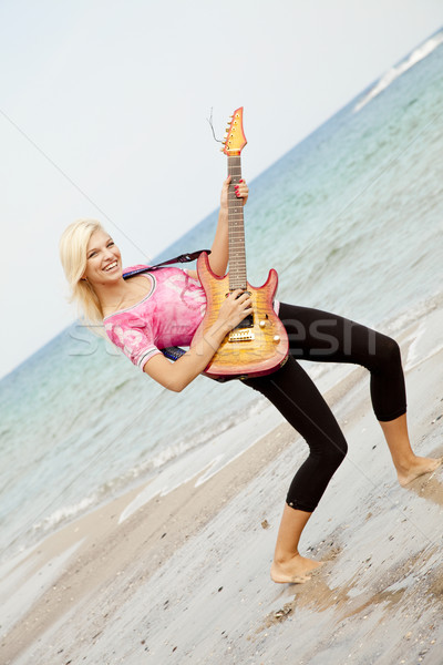 Young blonde girl with guitar on the beach. Stock photo © Massonforstock