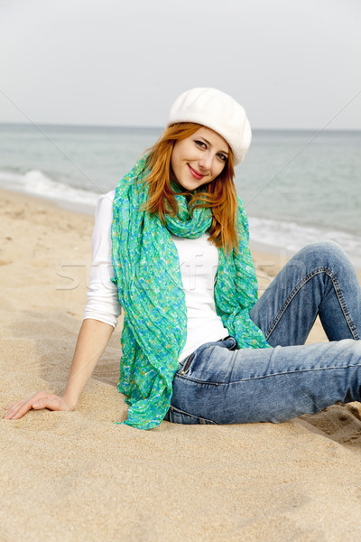 Young beautiful girl sitting at the beach Stock photo © Massonforstock