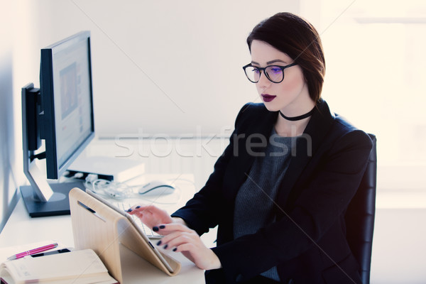 beautiful young woman sitting at the desk and typing text on tab Stock photo © Massonforstock