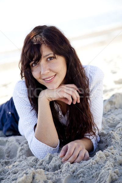 Pretty young woman lying down on beach Stock photo © Massonforstock