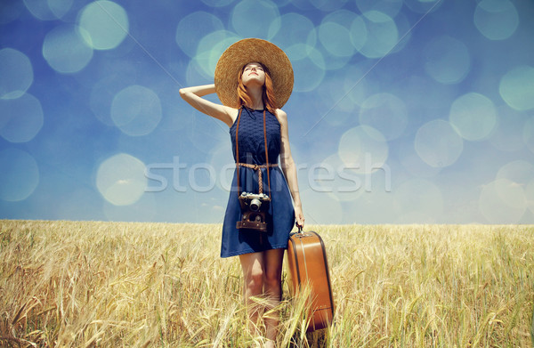 Redhead girl with suitcase at spring wheat field. Stock photo © Massonforstock