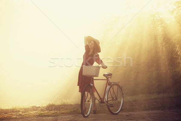 Girl on a bike in the countryside in sunrise time Stock photo © Massonforstock