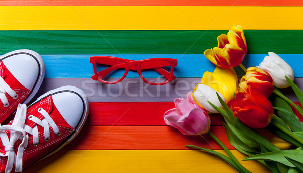 bunch of tulips, red gumshoes and red glasses lying on the table Stock photo © Massonforstock
