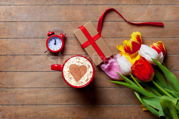 bunch of tulips, red clock, gift and a cup of coffee lying on th Stock photo © Massonforstock