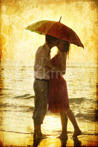 Couple kissing under umbrella at the beach in sunset. Stock photo © Massonforstock