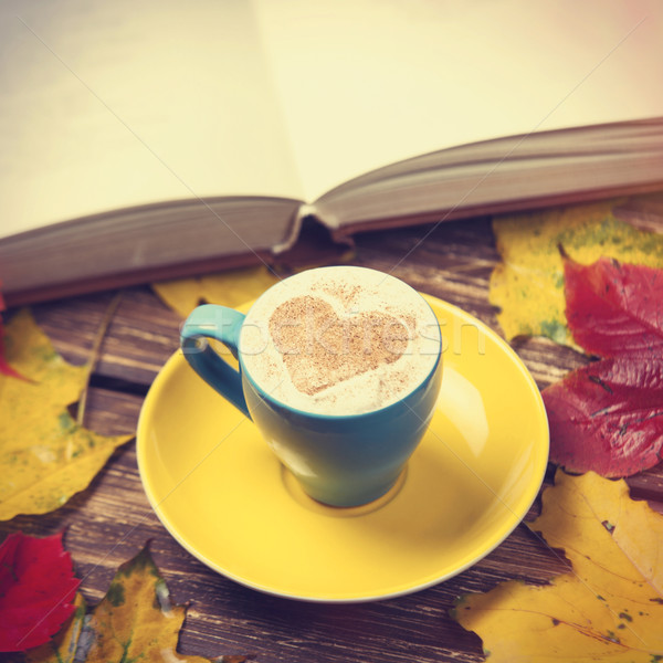 Autumn leafs, book and coffee cup on wooden table. Stock photo © Massonforstock