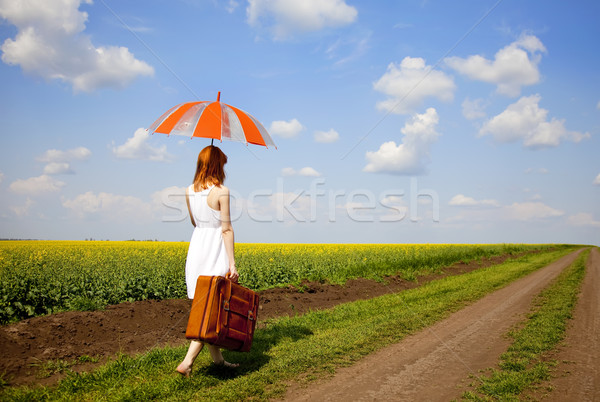 Redhead enchantress walking near rapeseed field. Stock photo © Massonforstock