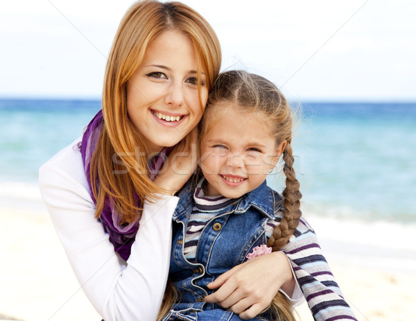 Two sisters 5 and 22 years old at the beach in sunny autumn day Stock photo © Massonforstock