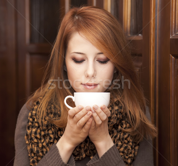 Style redhead girl drinking coffee near wood doors. Stock photo © Massonforstock