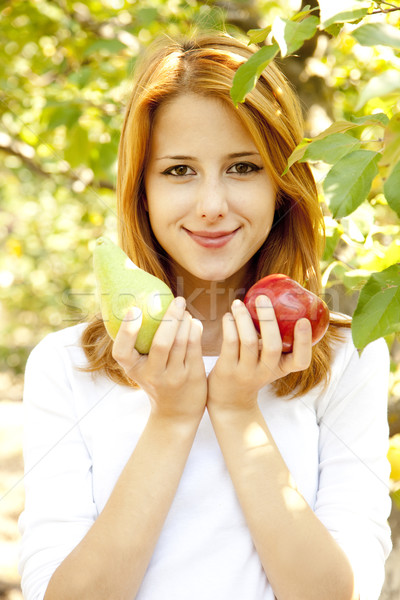 Beautiful young redhead woman standing near the apple tree. Stock photo © Massonforstock