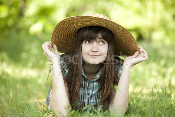 Young fashion girl in white hat at green spring grass. Stock photo © Massonforstock