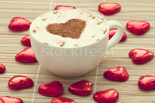 Stock photo: Cup of coffee with heart symbol and candy around.