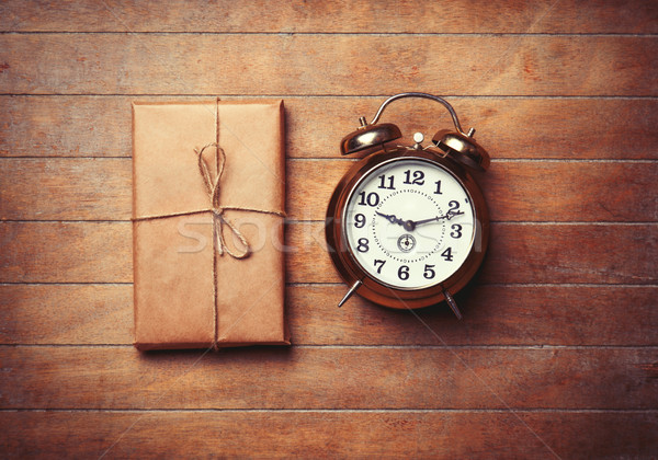Retro alarm clock and package on wooden table. Stock photo © Massonforstock
