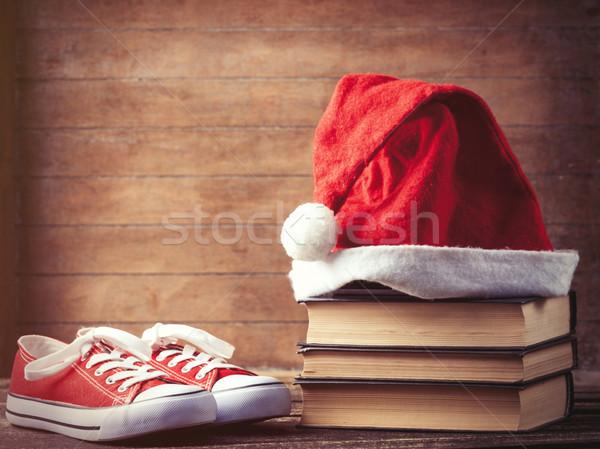 Santas hat over books near red gumshoes  Stock photo © Massonforstock