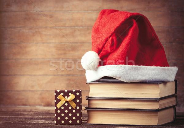 Santas hat over books near gift box  Stock photo © Massonforstock