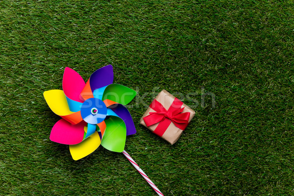 Multi colored pinwheel and little gift box on spring green glass Stock photo © Massonforstock