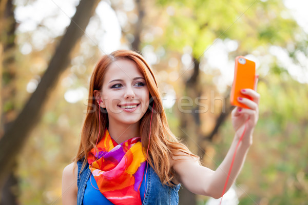 beautiful young woman holding her mobile phone and taking selfie Stock photo © Massonforstock