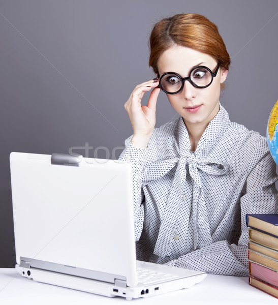 Stock photo: The young teacher in glasses with books, globe and notebook.