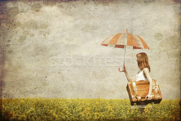 Redhead enchantress with umbrella and suitcase at spring rapesee Stock photo © Massonforstock
