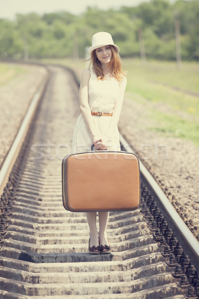 Young fashion girl with suitcase at railways. Stock photo © Massonforstock