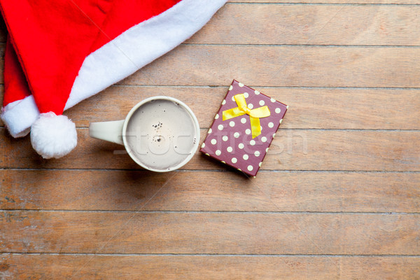 cup of coffee, gift and santa claus hat on the wonderful brown w Stock photo © Massonforstock