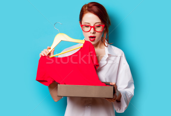 photo of beautiful young woman with shirt on hanger under box on Stock photo © Massonforstock