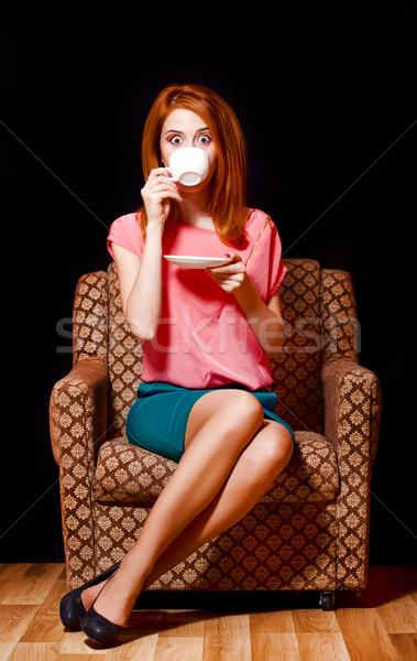 Surprised redhead girl with cup of coffee. 70s Stock photo © Massonforstock