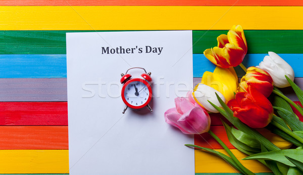 bunch of tulips, little red clock and sheet of the paper lying o Stock photo © Massonforstock